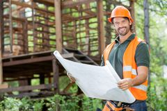 Happy Male Architect Holding Blueprint At Site stock image