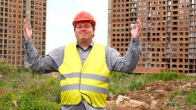 Male builder foreman, worker or architect on construction building site proudly shows results while raising his arms. Happy male builder foreman, worker or stock video footage