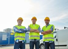 Happy male builders in high visible vests outdoors. Industry, building, construction and people concept - happy male builders in high visible vests outdoors stock photography