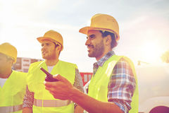 Happy male builders in vests with walkie talkie Stock Photo