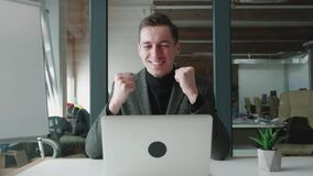 Happy male businessman gets great news on his laptop computer. Excited man office worker celebrate success win and