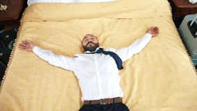 Happy male businessman jumping on bed at hotel room having business trip slow motion stock footage