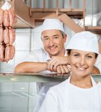 Happy Male Butcher With Colleague At Butchery Stock Images