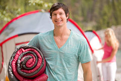 Happy Male Camper. A portrait of a happy male camper holding a sleeping bag stock image