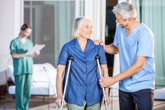 Happy Male Caretaker Helping Senior Woman In Stock Photography