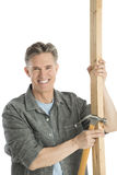 Happy Male Carpenter Holding Hammer And Wooden Plank Royalty Free Stock Photo