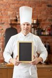 Happy male chef with blank menu board in kitchen Royalty Free Stock Photo
