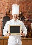 Happy male chef with blank menu board in kitchen Stock Photo