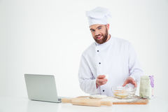Happy male chef cook baking with laptop Stock Photos