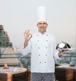 Happy male chef cook with cloche showing ok sign. Cooking, profession, gesture and people concept - happy male chef cook holding cloche and showing ok sign over Stock Images