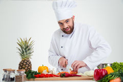 Happy male chef cook cutting vegetables Royalty Free Stock Image