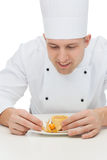 Happy male chef cook decorating dessert Stock Image