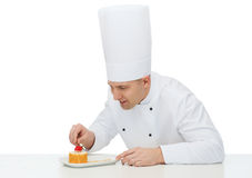 Happy male chef cook decorating dessert Stock Photo