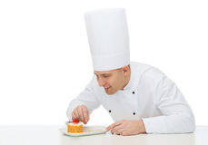 Happy male chef cook decorating dessert Royalty Free Stock Images