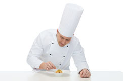 Happy male chef cook decorating dish. Cooking, profession, haute cuisine, food and people concept - happy male chef cook decorating dish Royalty Free Stock Image