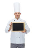Happy male chef cook holding blank menu board Royalty Free Stock Photos