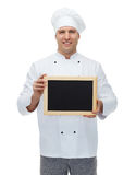 Happy male chef cook holding blank menu board Royalty Free Stock Photo