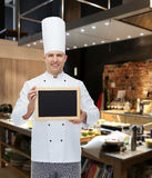 Happy male chef cook holding blank menu board Stock Photo