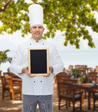 Happy male chef cook holding blank menu board. Cooking, profession, advertisement and people concept - happy male chef cook showing and holding blank menu board stock image