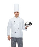 Happy male chef cook holding cloche Stock Images