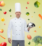 Happy male chef cook holding cloche Royalty Free Stock Image