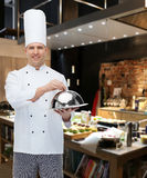 Happy male chef cook holding cloche. Cooking, profession and people concept - happy male chef cook holding cloche over restaurant kitchen Stock Images