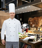 Happy male chef cook holding cloche Royalty Free Stock Photo