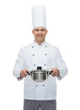 Happy male chef cook holding pot. Cooking, profession and people concept - happy male chef cook holding pot Royalty Free Stock Photos