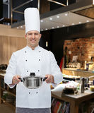 Happy male chef cook holding pot. Cooking, profession and people concept - happy male chef cook holding pot over restaurant kitchen Stock Photography