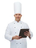 Happy male chef cook holding tablet pc Royalty Free Stock Image