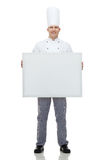 Happy male chef cook holding white blank big board. Cooking, profession, advertisement and people concept - happy male chef cook holding and showing white blank Royalty Free Stock Images