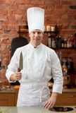Happy male chef cook in kitchen with knife Stock Photography