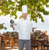 Happy male chef cook opening cloche Stock Photos