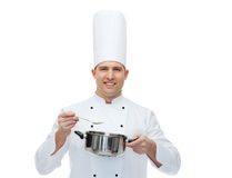 Happy male chef cook with pot and spoon. Cooking, profession and people concept - happy male chef cook with pot and spoon Royalty Free Stock Photos
