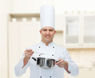 Happy male chef cook with pot and spoon. Cooking, profession and people concept - happy male chef cook with pot and spoon Royalty Free Stock Photography