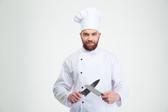Happy male chef cook sharpening knife. Portrait of a happy male chef cook sharpening knife isolated on a white background stock photos