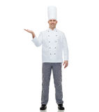 Happy male chef cook showing empty palm Royalty Free Stock Photo