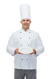 Happy male chef cook showing empty plate Royalty Free Stock Photos