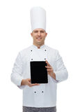 Happy male chef cook showing with tablet pc Royalty Free Stock Images