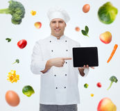 Happy male chef cook showing with tablet pc Stock Images