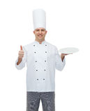 Happy male chef cook showing thumbs up and plate Stock Image
