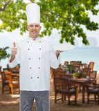 Happy male chef cook showing thumbs up and plate Stock Photography