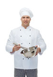 Happy male chef cook whipping something with whisk. Cooking, profession and people concept - happy male chef cook holding bowl and whipping something with whisk Stock Image