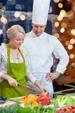 Happy male chef cook with woman cooking in kitchen Stock Images