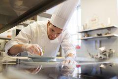 Happy male chef cooking food at restaurant kitchen Royalty Free Stock Photo