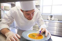 Happy male chef cooking food at restaurant kitchen Stock Images