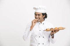 A happy male chef eating cookies Royalty Free Stock Photography