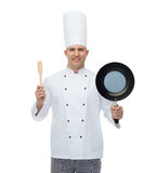 Happy male chef holding frying pan and spatula Stock Photos