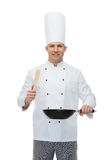 Happy male chef holding frying pan and spatula Royalty Free Stock Photography