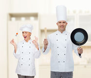 Happy male chef holding frying pan and spatula Royalty Free Stock Photo